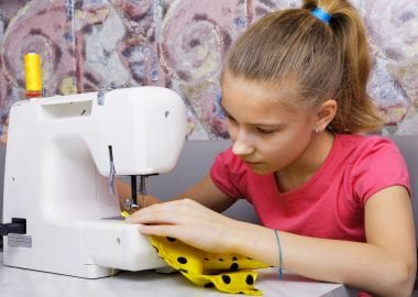 73400311 - girl learns to sew on an electric sewing machine